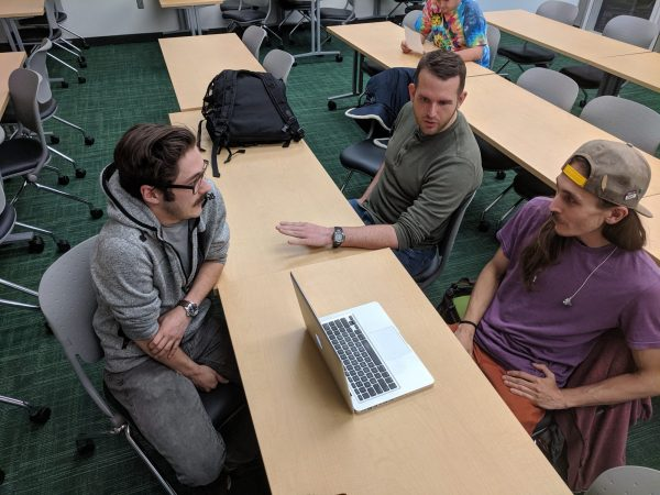 three students talking at a table in a classroom